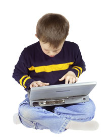 Young boy sitting crossed legged using wireless laptop