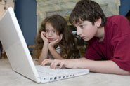 Girl and boy using laptop at home