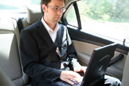 Man in car working on laptop using mobile Broadband
